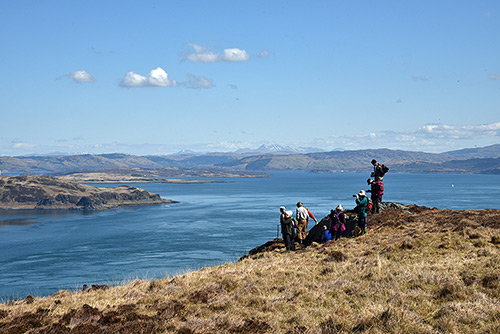Picture of a group of walkers high above a gulf between two islands