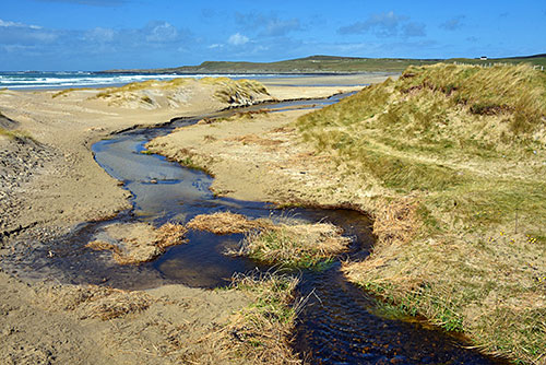 Picture of a burn (river) meandering across a beach