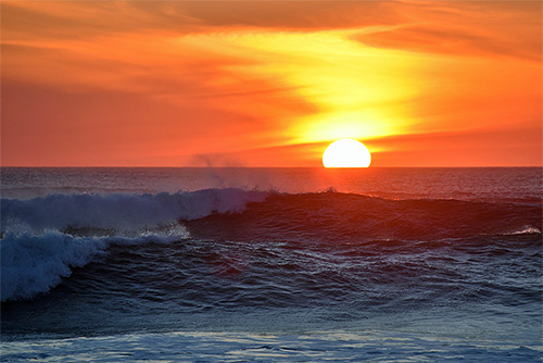 Picture of a sunset behind breaking waves